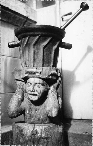 Mortier, billot : mortier en fonte à poignées, billot en bois sculpté d'un buste de personnage (face)