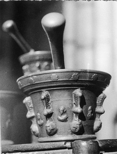 Mortier : mortier de pharmacie en bronze, décor en relief de têtes de femmes, de frise de fleurs