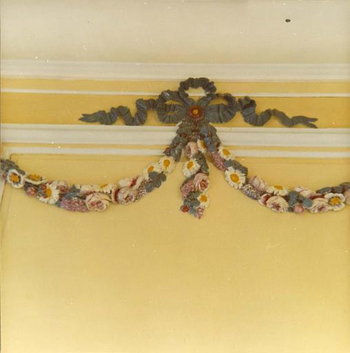 Lambris de revêtement : détail d'une guirlande de fleurs en bois sculpté et peint, d'époque Louis XVI ; après restauration