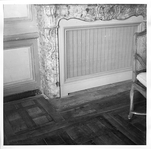 Cheminée en marbre fermée par une grille, état antérieur à la restauration de l'ensemble de la pièce