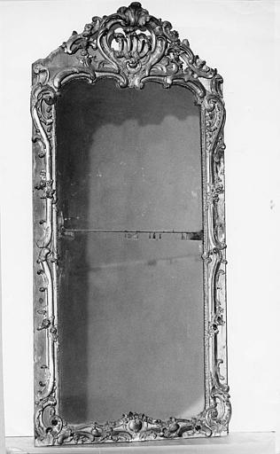 Glace de trumeau : cadre en bois sculpté de volutes, de motifs végétaux et surmonté d'une coquille ajourée, doré, miroir manquant