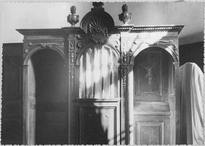 Confessionnal : bois sculpté de chutes de fleurs et volutes, surmonté par une coquille et deux pots à feu