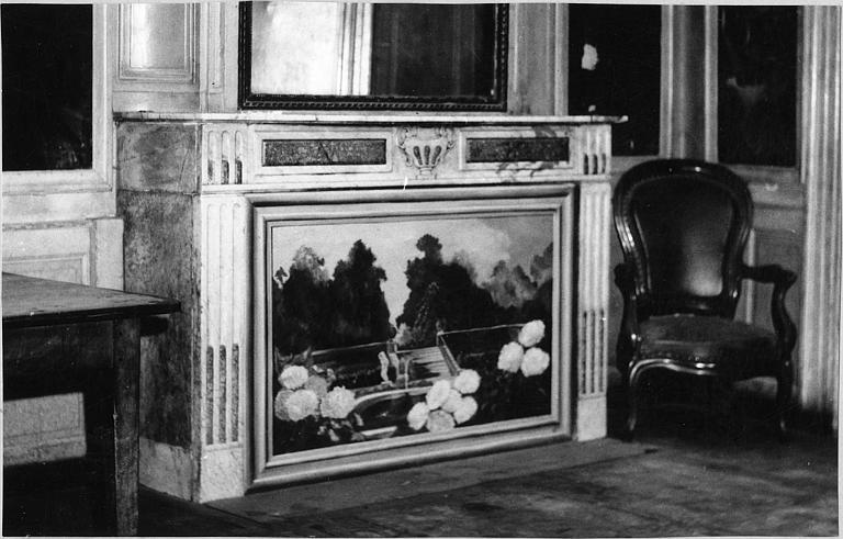 Cheminée : cheminée à montants droits, marbre polychrome, linteau gravé d'un vase, foyer fermé par un tableau représentant un paysage