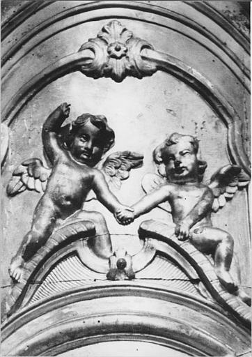 Tabernacle : détail de deux angelots sculptés en bas-relief au-dessus de la porte du tabernacle, bois sculpté, doré