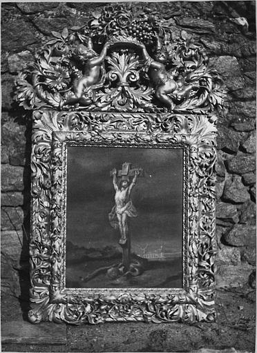Cadre : cadre à fronton, bois sculpté de motifs végétaux et putti portant une corbeille de fleurs