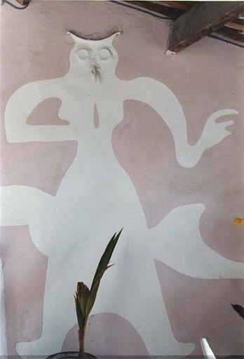 Peinture monumentale, relief : personnage peint à tête de hibou en relief