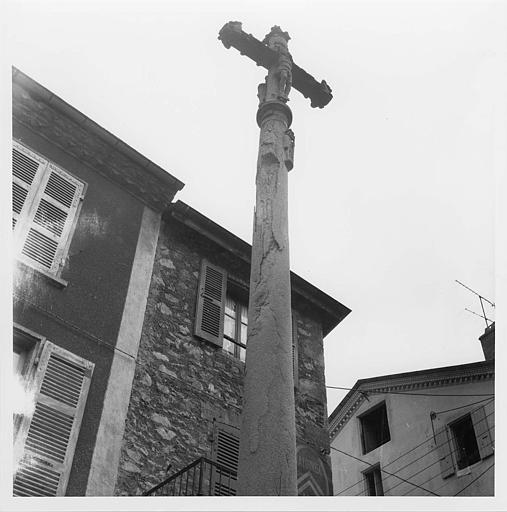 Croix de chemin : pierre sculptée d'un Christ en croix et de petits personnages en demi-relief