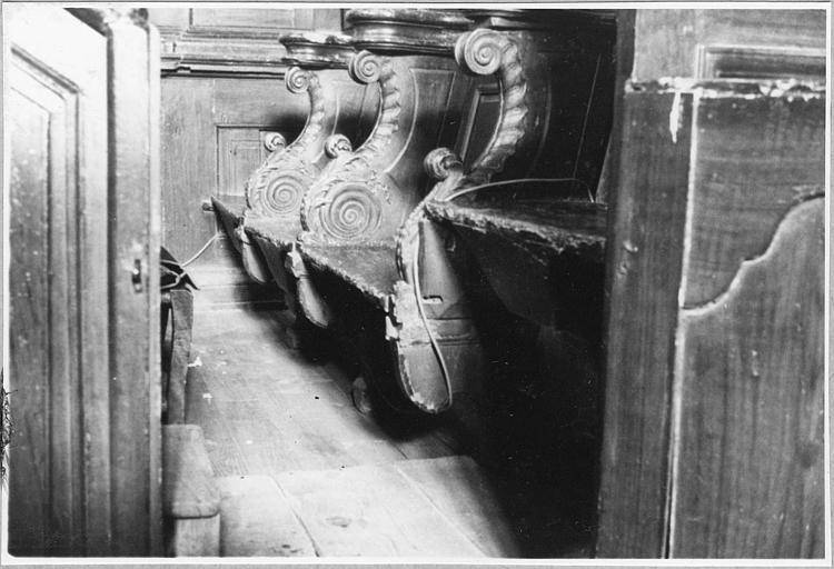 Stalles : détail des bancs et des parecloses sculptées de volutes ; avant restauration