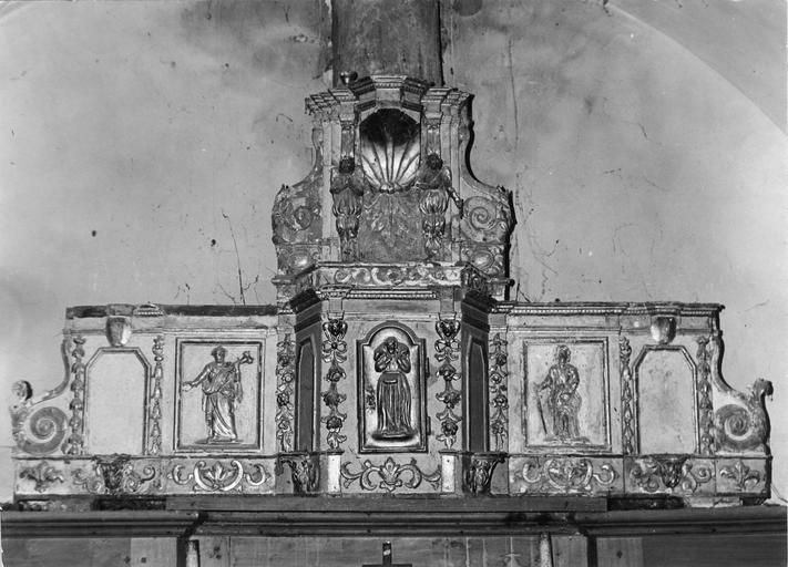 Tabernacle architecturé surmonté d'une exposition, décor de demi-reliefs représentant saint Pierre, saint Paul, et au centre, le Bon Pasteur, chutes de fleurs et de feuilles, rinceaux, bois sculpté, peint, doré