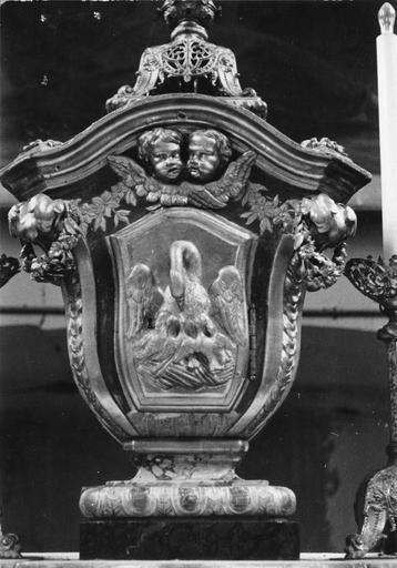 Tabernacle en forme de vase surmonté d'une corniche, à la porte sculptée du pélican nourrissant ses petits et surmontée de deux chérubins, décor de guirlandes de fleurs, bois sculpté, peint, doré