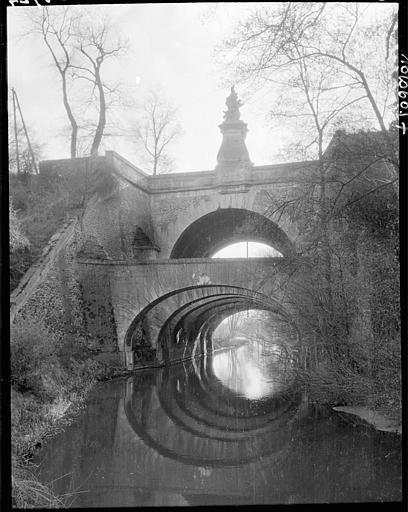 Vue d'ensemble : arches, fontaine, reflets dans l'eau
