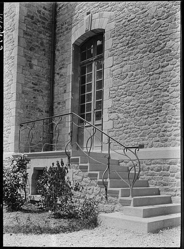 Porte d'entrée et escalier à la rampe en fer forgé
