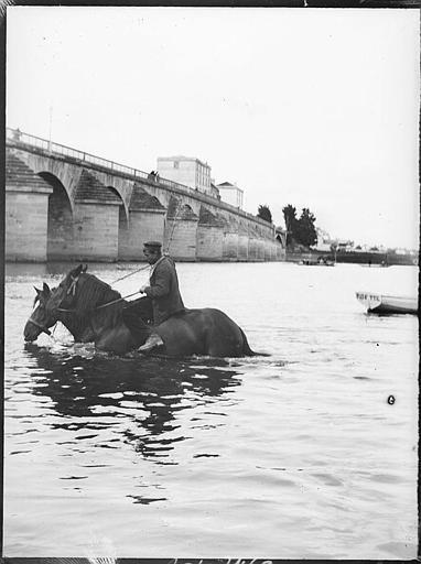 Ancien pont à arches : homme à cheval dans le fleuve
