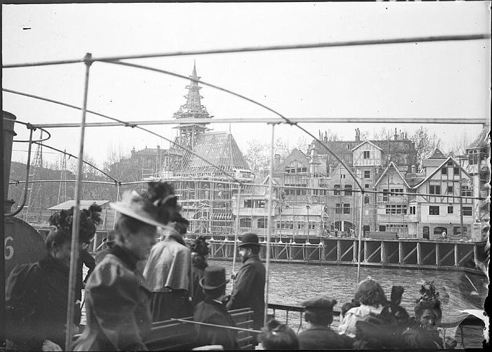 Construction des pavillons vue d'un bateau sur la Seine, passagers