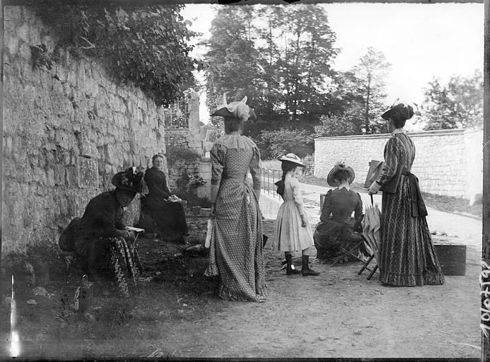 Groupe de femmes devant un mur en pierres