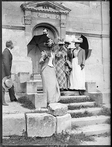 Groupe de personnes posant sur les marches d'un escalier, porte à fronton