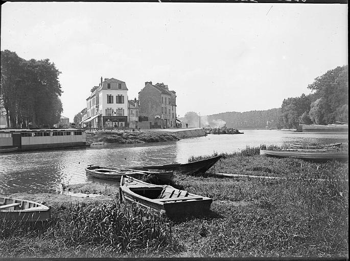 Barques sur une berge de l'Oise, immeubles sur la rive opposée