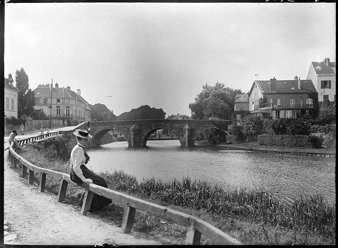 Pont sur l'Oise, femme assise sur une rambarde de la rive, maisons