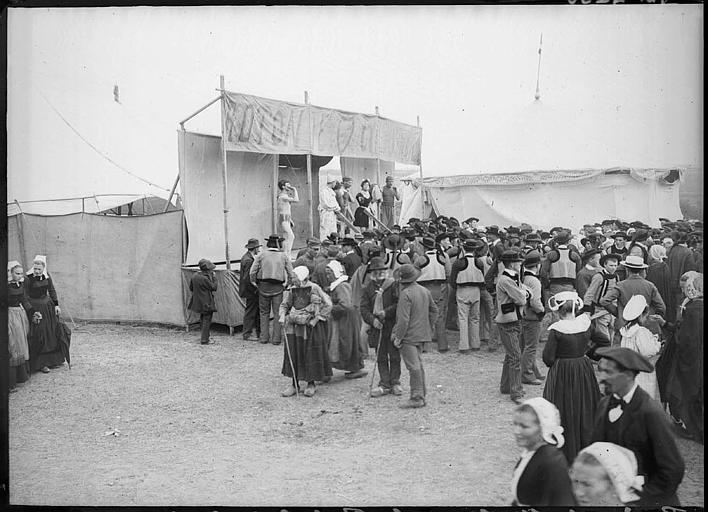 Pardon breton du dernier dimanche d'août : une foule de pèlerins en costume traditionnel devant une estrade
