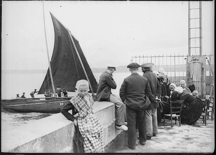 Bretons en costume traditionnel sur la jetée, voilier en mer