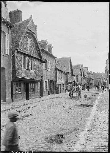 Rue animée : maisons anciennes, attelages de chevaux et personnages