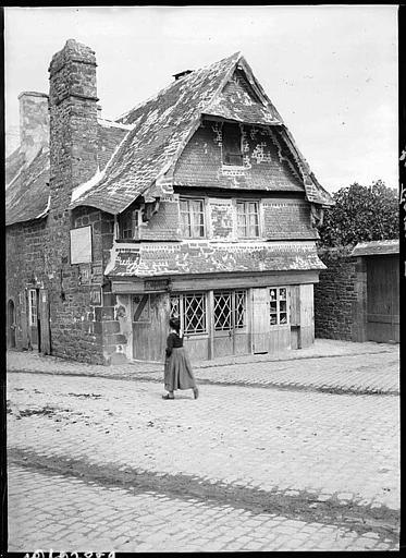 Maison en pierres : façade sur rue, bretonne en costume traditionnel
