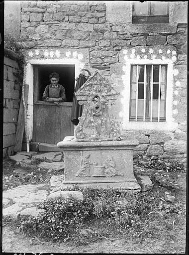 Puits en pierre, fermière accoudée à une porte fermière