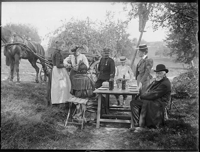 Repas champêtre : groupe de personnes attablées, attelage de chevaux