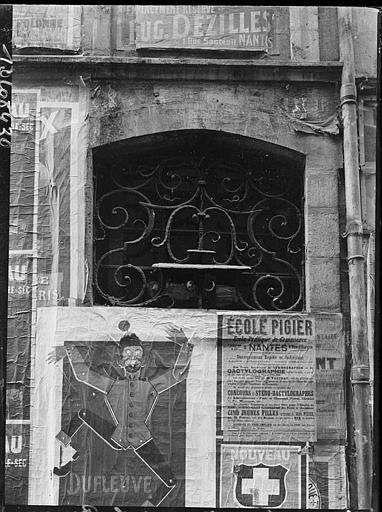 Porte : imposte en fer forgé, affiches publicitaires
