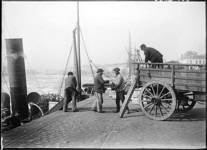 Hommes déchargeant des marchandises d'une charrette à un bateau