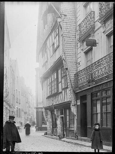 Rue pavée : maisons anciennes, passants