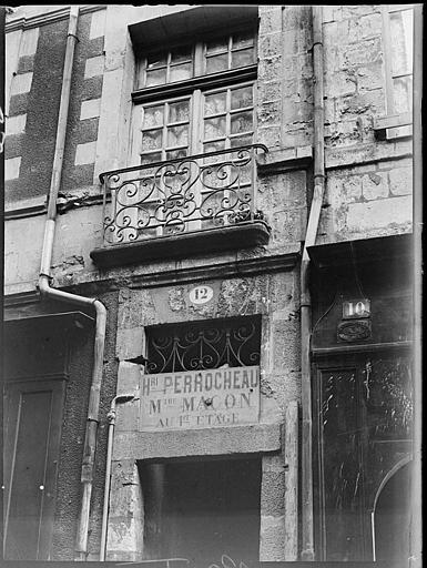 Devanture de boutique : imposte de porte et balcon en fer forgé
