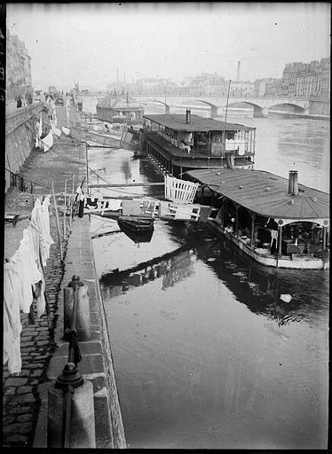 Sur le quai : péniches amarrées, linge étendu, pont à l'arrière-plan