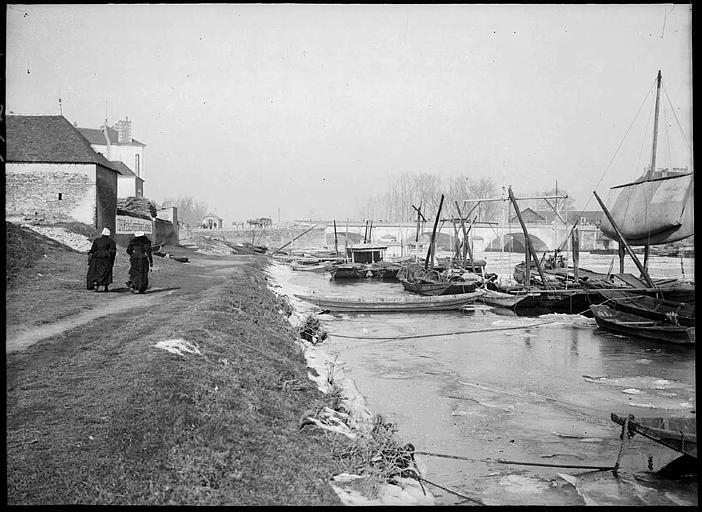 Sur la berge : péniche, barques, pont à l'arrière-plan