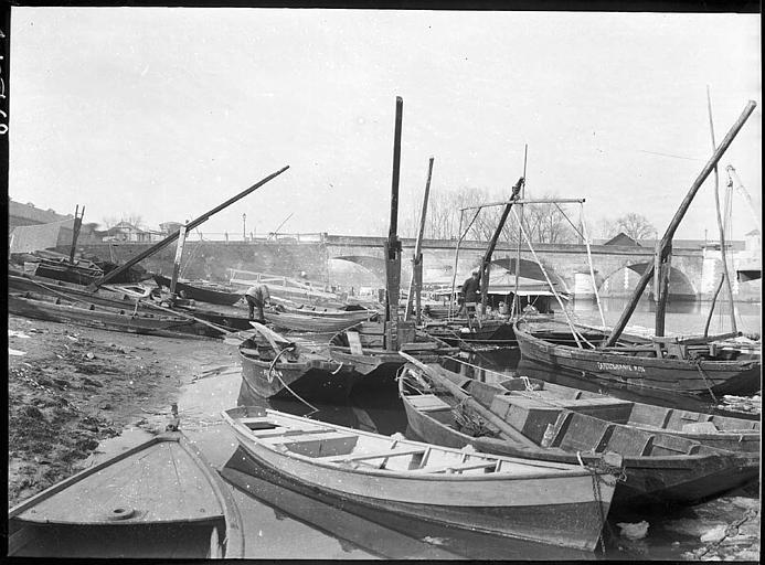 Sur la berge : barques et bateaux de pêche, pont à l'arrière plan