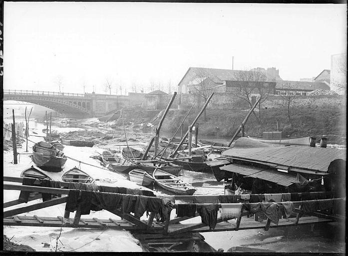 Sur la berge : péniche amarrée, barques, pont à l'arrière-plan