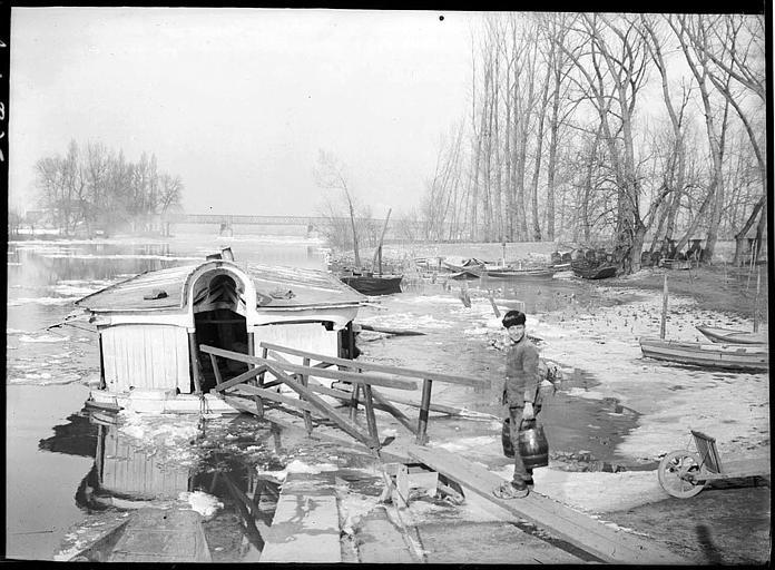 Marinier sur un ponton, péniche amarrée, pont à l'arrière-plan