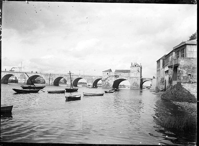 Vue d'ensemble : arches, maisons sur les bords du fleuve, barques sur le fleuve