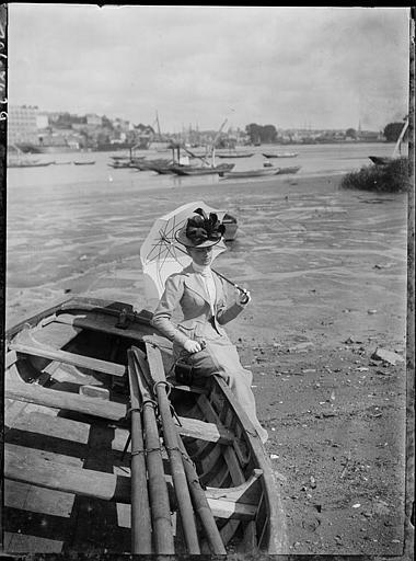 Sur la berge, femme adossée à une barque