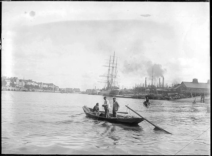 Hommes sur une barque au milieu du fleuve, grands voiliers et maisons à l'arrière-plan