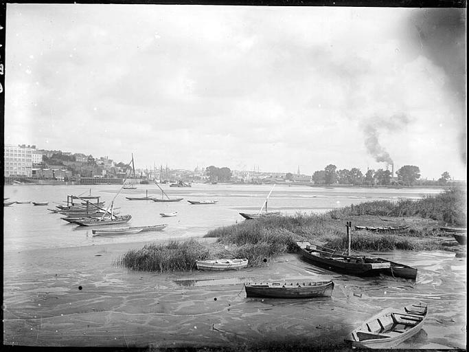 Barques sur le fleuve, grands voiliers à l'arrière-plan
