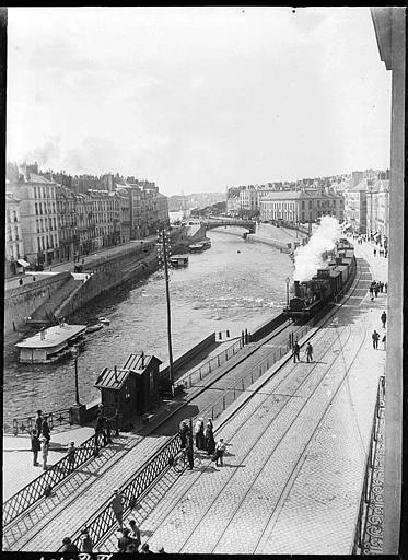 Vue plongeante sur le canal : train de marchandises, passants