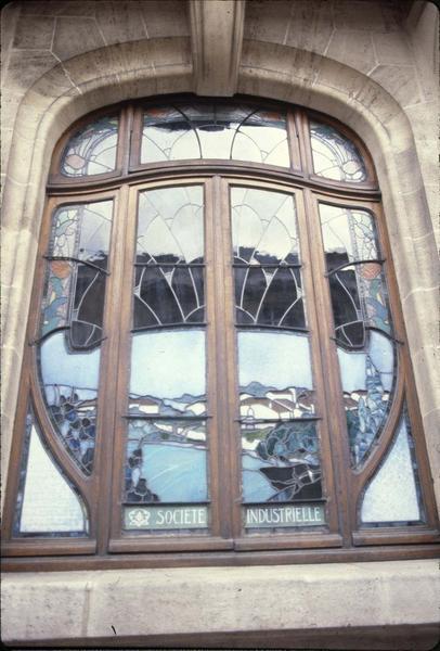 Fenêtre du rez-de-chaussée sur rue avec vitrail
