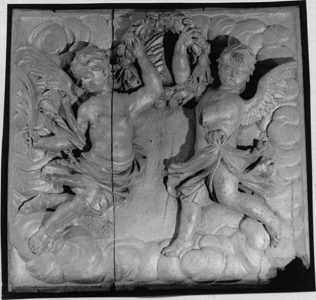 2 reliefs encadrés : couples d'anges tenant une couronne de fleurs et un livre ouvert