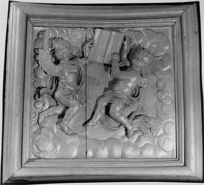 Relief sculpté : deux angelots sur une nuant tenant un livre
