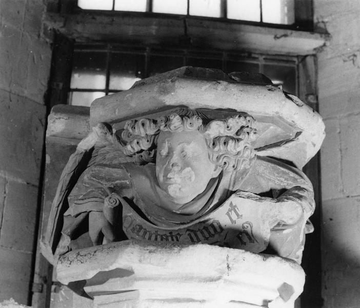culot : ange accroupi sous la base d'une colonne, déroulant un phylactère