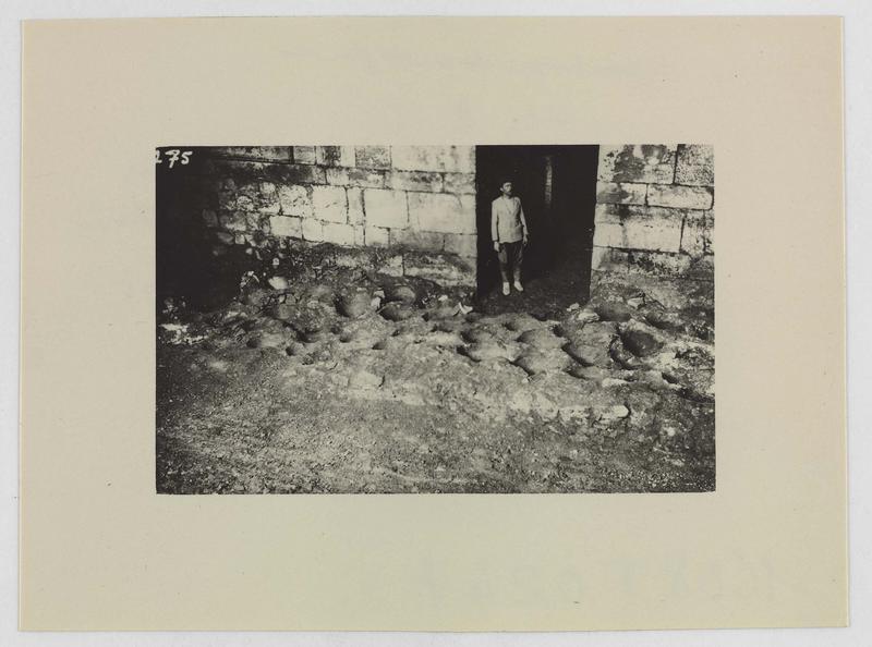 Traces d'amphores enterrées dans le sol d'une salle, avec un personnage