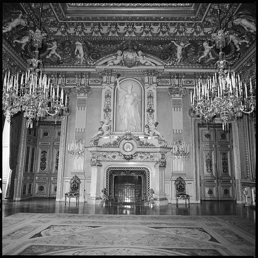 Salon orné d'une cheminée monumentale, et plafond décoré de putti