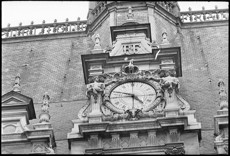 Partie supérieure : horloge monumentale flanquée de deux cariatides en gaine avec bras