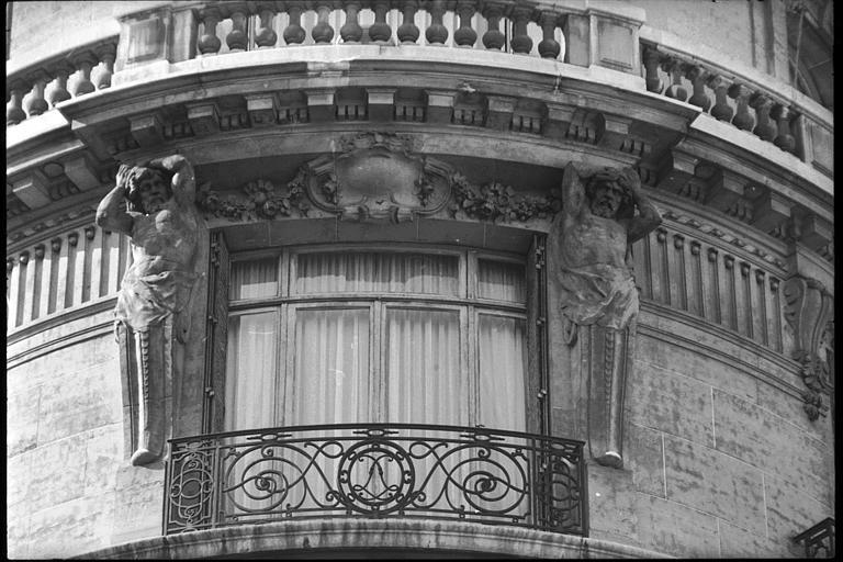 Angle de deux façades orné de deux atlantes en gaine avec bras : vue rapprochée